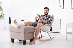 Man with broken leg in cast using mobile phone. While sitting in armchair at home stock photo