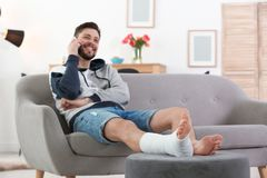 Man with broken leg in cast using mobile phone. While sitting on sofa at home stock photo