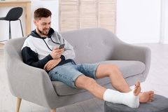 Man with broken leg in cast using mobile phone. While sitting on sofa at home stock photos