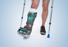 Man with a broken leg with Crutches on a blue background Stock Photography