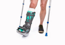 Man with a broken leg with Crutches on a white background Royalty Free Stock Photos
