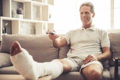 Man with broken leg Stock Images