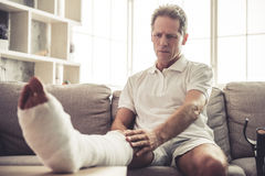 Man with broken leg. Handsome mature man is touching his broken leg in gypsum while sitting on sofa at home Stock Photo