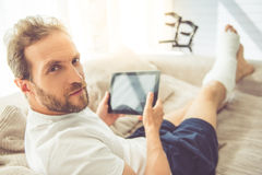 Man with broken leg. Handsome man with broken leg is using a digital tablet, looking at camera and smiling while sitting on couch at home Royalty Free Stock Images