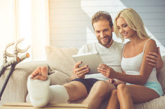 Man with broken leg and his wife. Handsome men with broken leg and his beautiful girlfriend are using a digital tablet and smiling while sitting on couch at home Stock Images