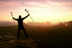 Man with broken leg and medicine crutch.  Hiker with leg in immobilizer achieve peak Royalty Free Stock Photos