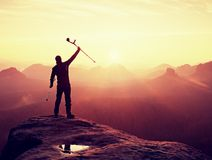 Man with broken leg and medicine crutch.  Hiker with leg in immobilizer achieve peak Royalty Free Stock Images
