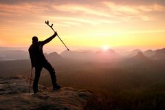 Man with broken leg and medicine pole above head stay on peak. Royalty Free Stock Image