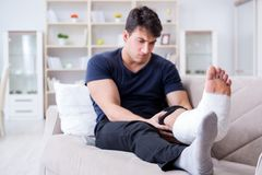 The man with broken leg recovering at home stock photography
