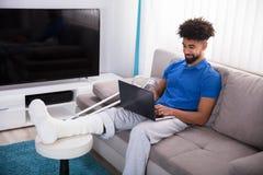 Man With Broken Leg Using Laptop. Man With Broken Leg Sitting On Sofa Using Laptop royalty free stock photo