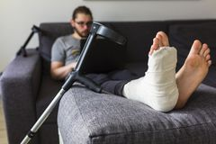 Man with a broken leg is surfing the internet. Young man with a broken leg is sitting on the sofa at home stock photo