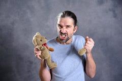 Man with broken teddy bear looking bad Stock Photography