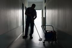 Man with broom cleaning office corridor Royalty Free Stock Photo