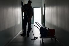 Man with broom cleaning office corridor. Full length of silhouette man with broom cleaning office corridor Stock Photos
