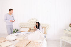 Man brought girl coffee breakfast in bed, husband cares for wife Royalty Free Stock Photo