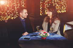 Man brought his girlfriend in a restaurant. Young couple having romantic dinner together in a restaurant drinking champagne royalty free stock photography