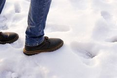 Man in brown boots and blue jeans desided to make first step to obscurity on the snow. Copy space. First step after snow stock photo