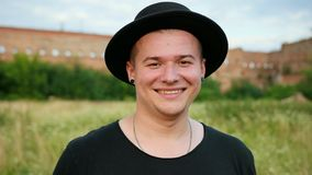 Man with brown eyes, black hat, earrings in his ears, posing, looking at camera. Young man, with brown eyes, in black hat and dark t-shirt, with earrings in stock video