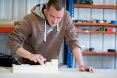 Man in Brown Hoodie Smearing White Paint on Plaster Model stock image