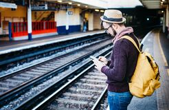 Man in Brown Hoodie Standing in Front of Train Railway Stock Photo