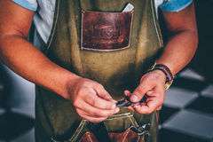 Man in Brown Leather Overalls Holding Black Tool Royalty Free Stock Photos