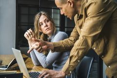 Man in Brown Long-sleeved Button-up Shirt Standing While Using Gray Laptop Computer on Brown Wooden Table Beside Woman in Gray Lon Stock Images
