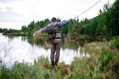 Man in Brown Pants Casting Fishing Rod Into Lake Stock Photos
