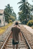Man in Brown Shirt Standing on Train Rail Near Coconut Palms Stock Photography