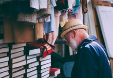 Man in Brown Sun Hat Facing Black Covered Piled Books Royalty Free Stock Photos