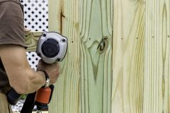 Handyman installs a fence with a pneumatic gun stock photos