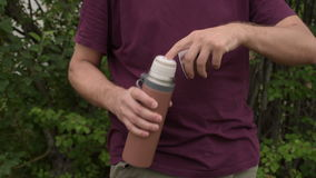 Man with a brown thermos outdoors stock video footage