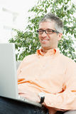 Man browsing internet. Happy man wearing orange shirt sitting on couch, browsing internet on laptop computer, smiling Royalty Free Stock Photography