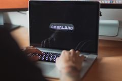 Man browsing on laptop, ready to download, button on screen royalty free stock photo