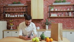 Man browsing on mobile phone at home kitchen. Handsome young man browsing on smartphone smiling happy. A man eats an stock footage