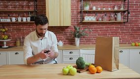 Man browsing on mobile phone at home kitchen. Handsome young man browsing on smartphone smiling happy. stock video