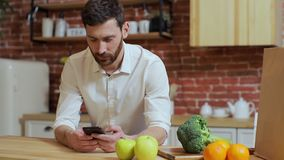 Man browsing on mobile phone at home kitchen. Handsome young man browsing on smartphone smiling happy stock video footage