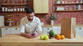 Man browsing on mobile phone at home kitchen. Handsome young man browsing on smartphone smiling happy. stock video footage
