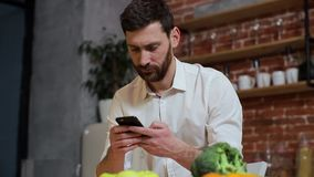 Man browsing on mobile phone at home kitchen. Handsome young man browsing on smartphone smiling happy. Man browsing on mobile phone at home kitchen. Handsome stock video footage