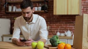 Man browsing on mobile phone at home kitchen. Handsome young man browsing on smartphone smiling happy. Man browsing on mobile phone at home kitchen. Handsome stock video