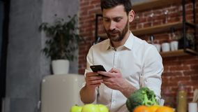 Man browsing on mobile phone at home kitchen. Handsome young man browsing on smartphone smiling happy. Man browsing on mobile phone at home kitchen. Handsome stock footage