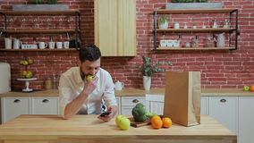 Man browsing on mobile phone at home kitchen. Handsome young man browsing on smartphone smiling happy. A man eats an. Apple and make photo stock video footage
