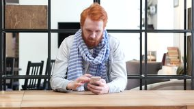 Man Browsing on Smartphone, Sitting in Office. Young creative designer , good looking stock video