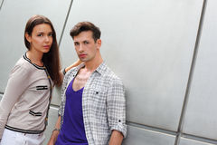 Man and brunette woman stand near gray wall Royalty Free Stock Images