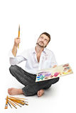 Man with brushes and palette  sitting. Isolated over white Royalty Free Stock Image