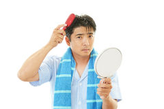 Man brushing his hair. Asian man wearing pajamas isolated on white background Royalty Free Stock Image