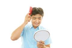 Man brushing his hair Stock Photo