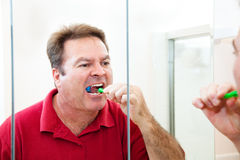 Man Brushing His Teeth in Bathroom Stock Photography