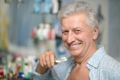 Man is brushing his teeth Stock Photo