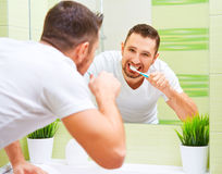 Man brushing his teeth with toothbrush in morning Stock Photo