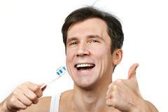 Man brushing his teeth Stock Images